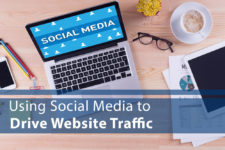 "Computer on Desk with Words ""Using Social Media to Drive Website Traffic"" over the image"